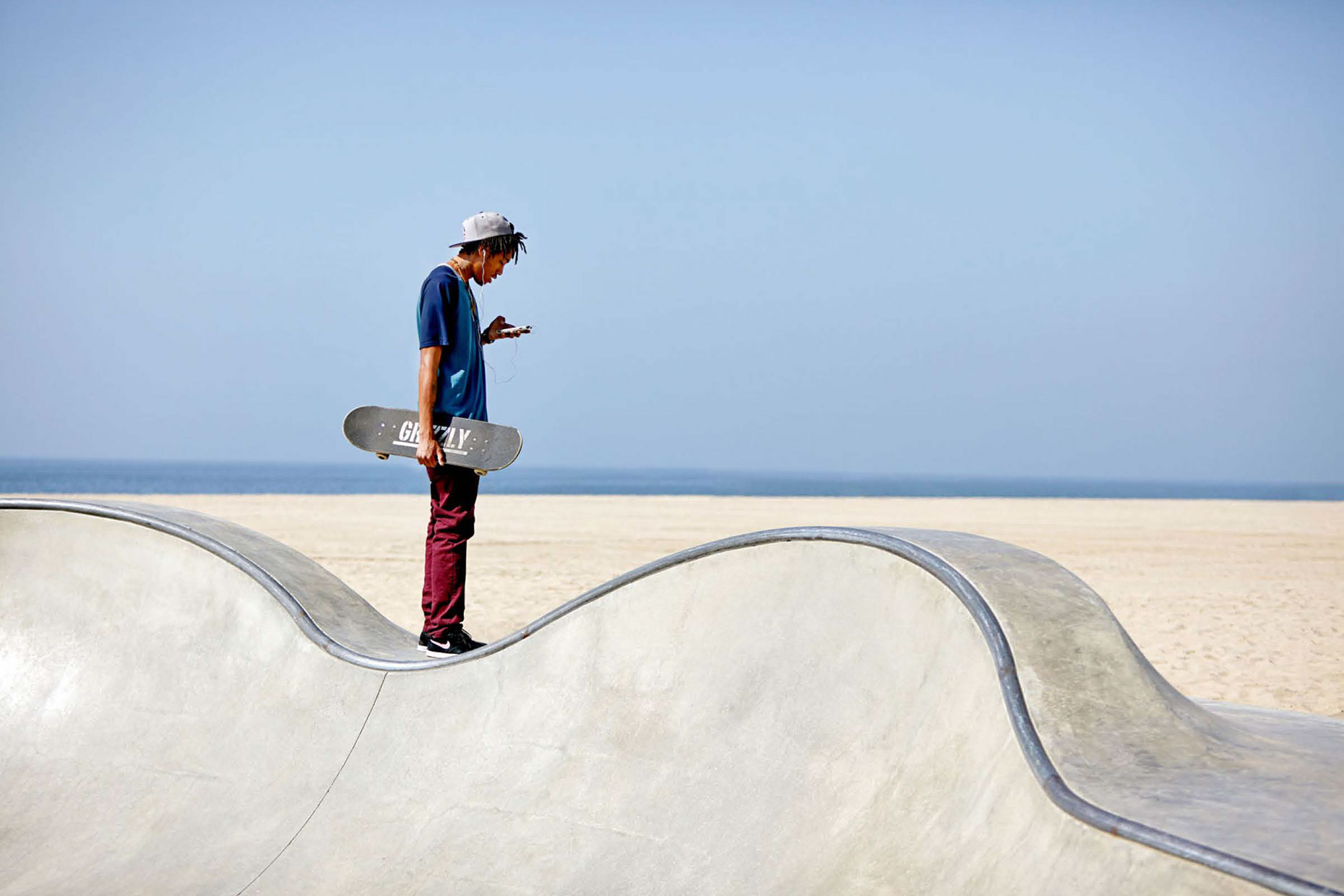 Photography_Lifestyle_Beach Skate Park Kid on Cell Phone-Tony Garcia