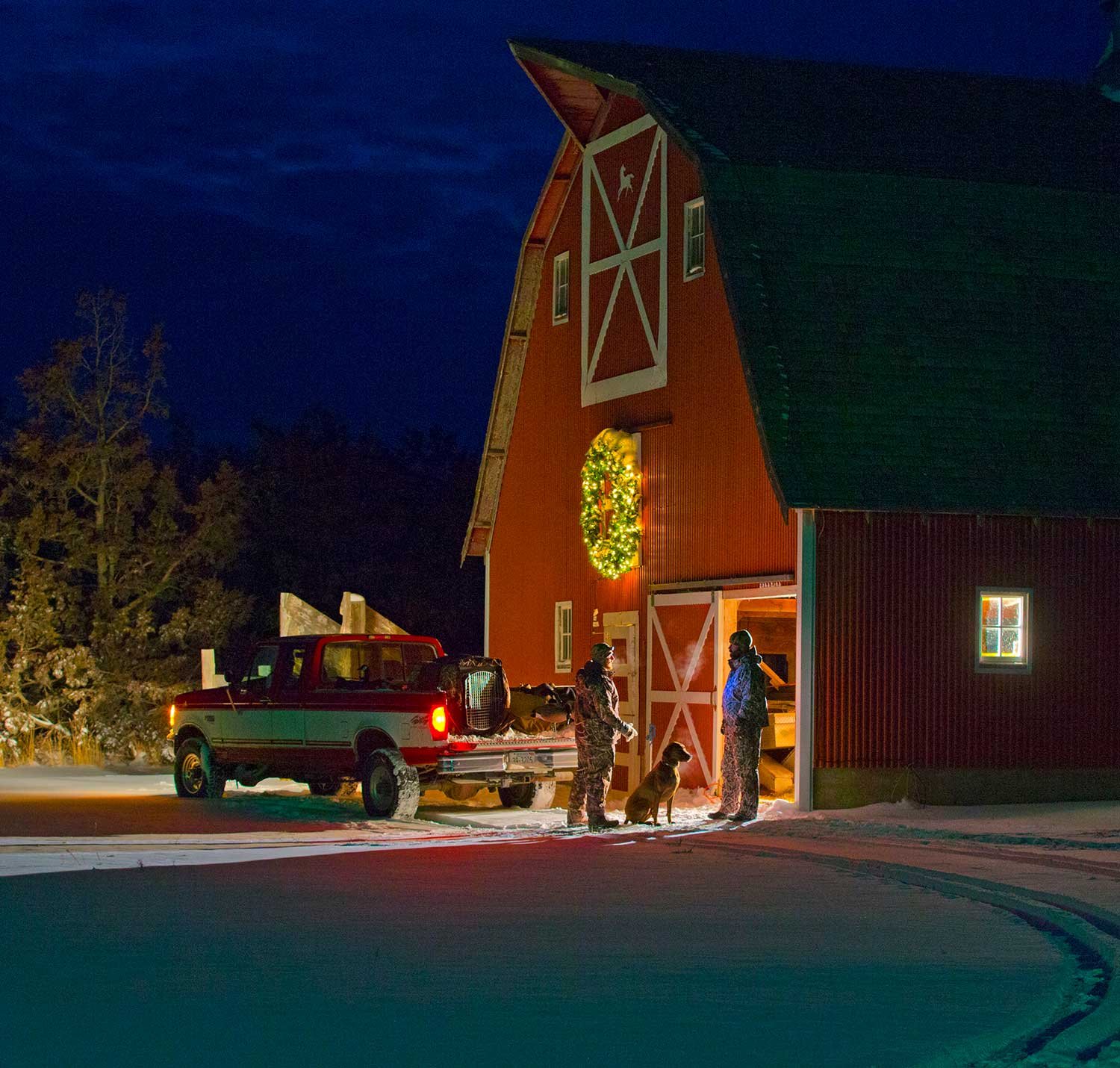 hunters in front of christmas barn with lit christmas wreath