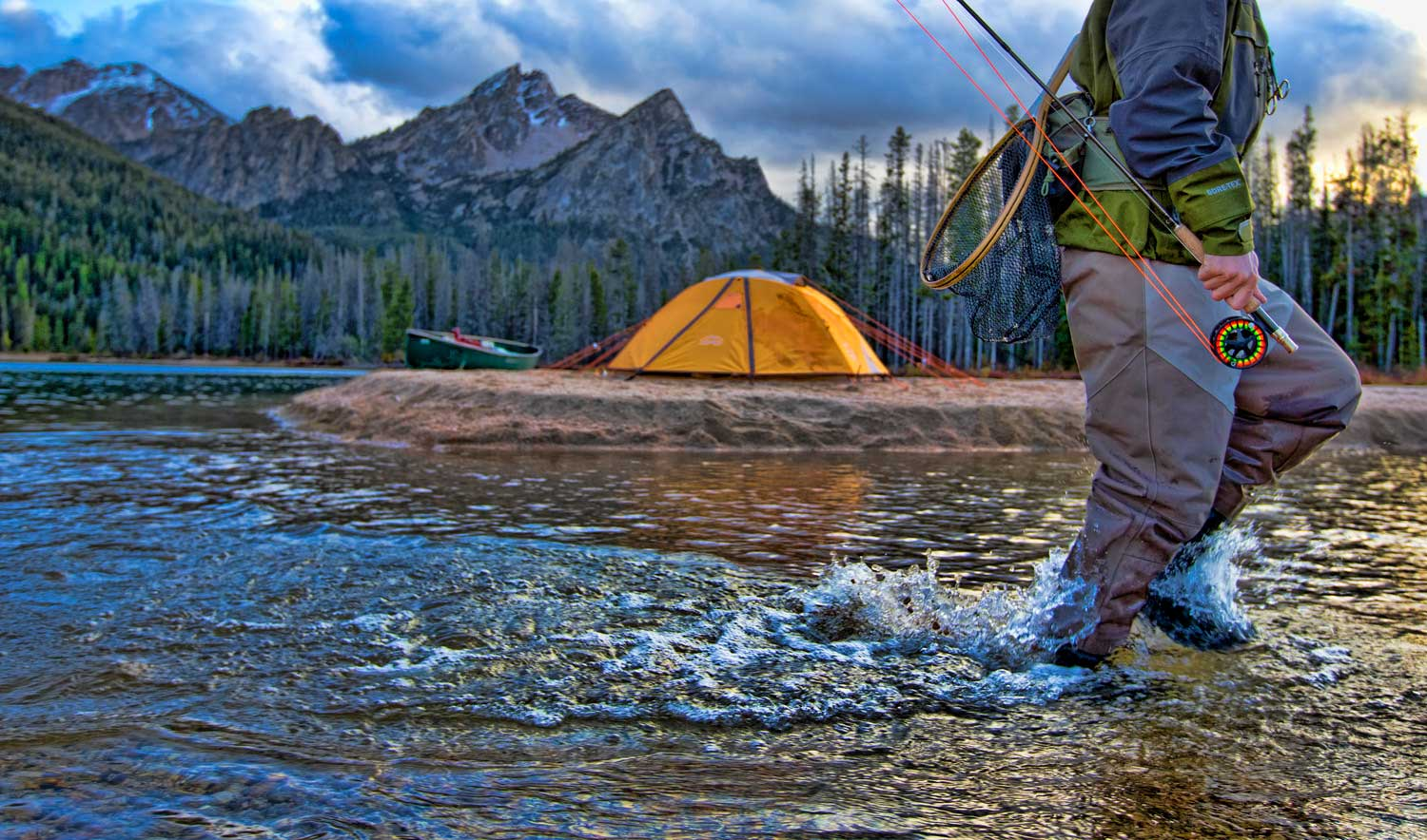 running-fly-fisherman-with-mountain-and-tent-back-drop