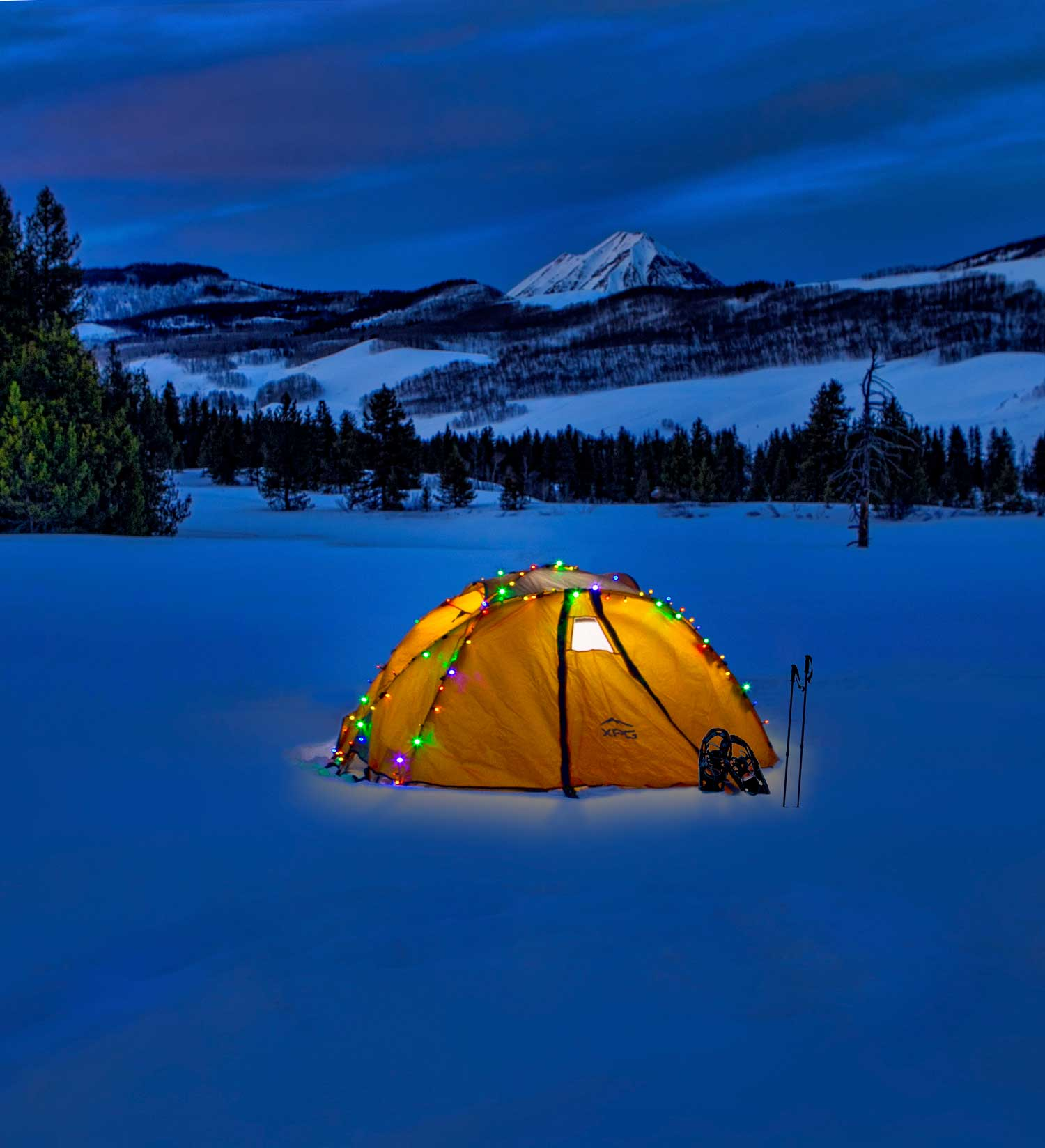 tent with lit up christmas lights on snowy mountain landscape