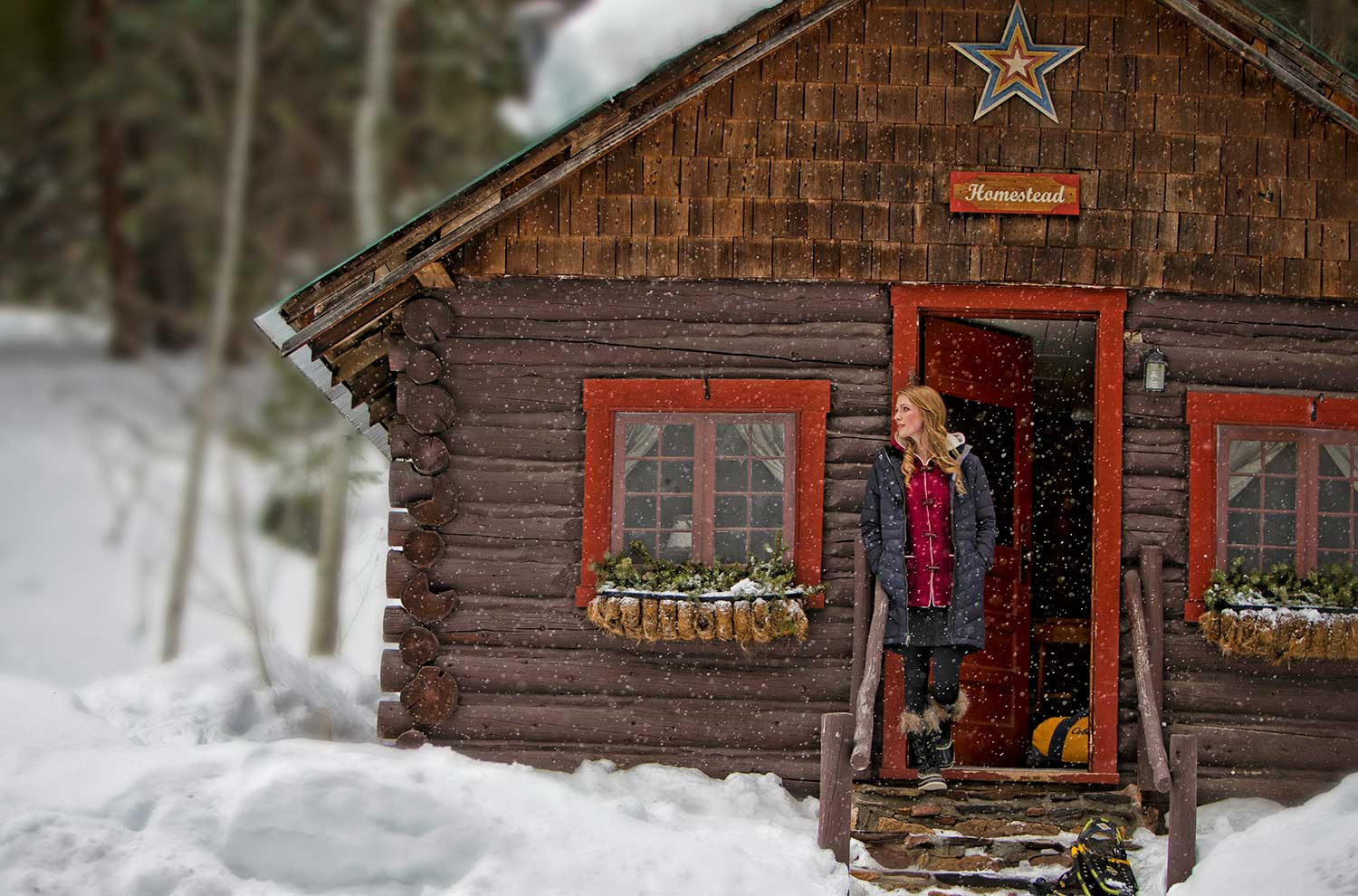 womant-in-doorway-of-homestead-cabin-with-snow-falling